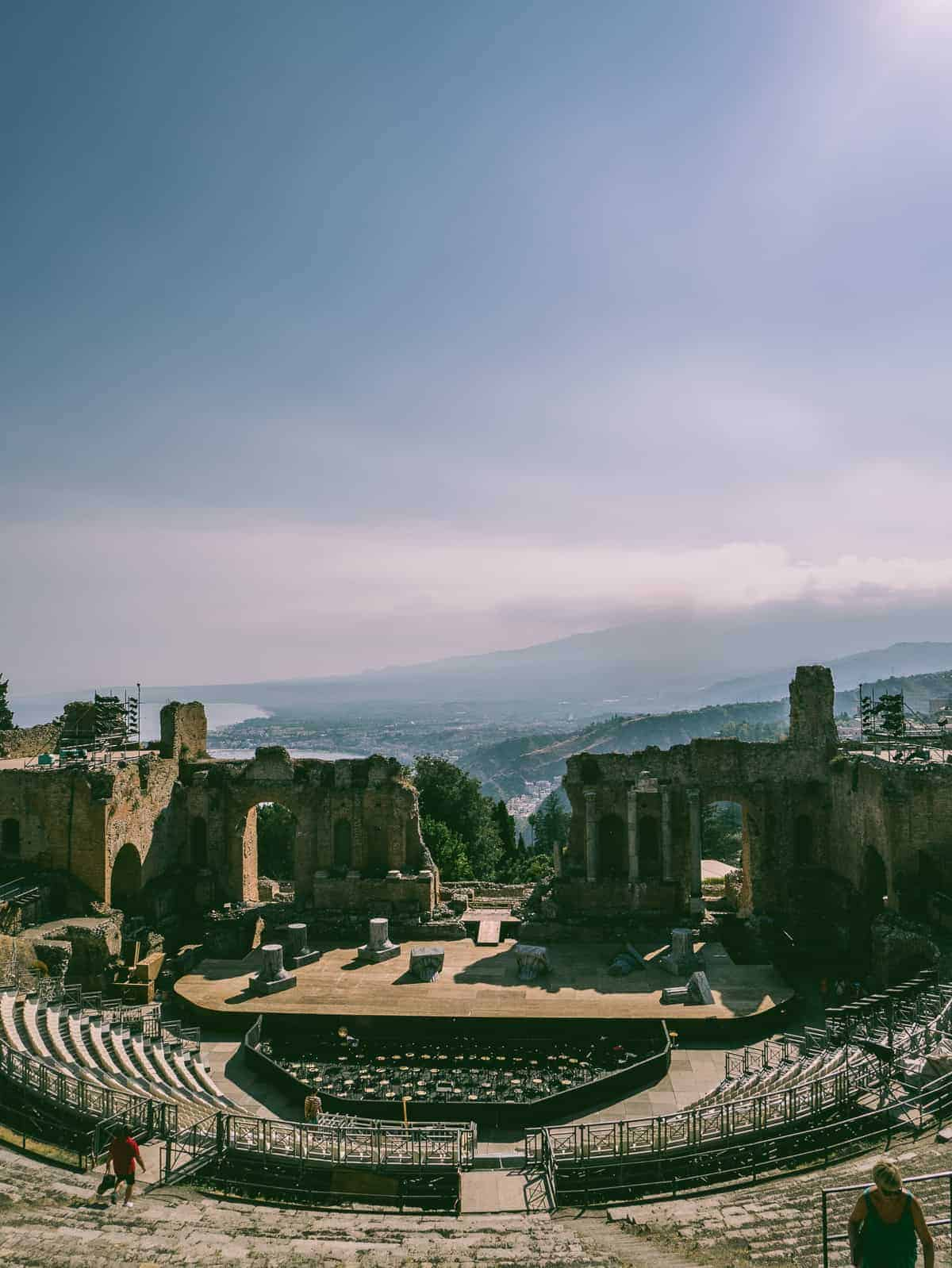 view of Taormina and amphitheatre steps located in Teatro Greco in Taormina Sicily