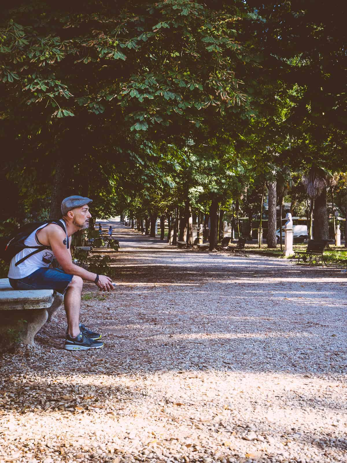 a person sitting on a park bench in the Villa Borghese Gardens