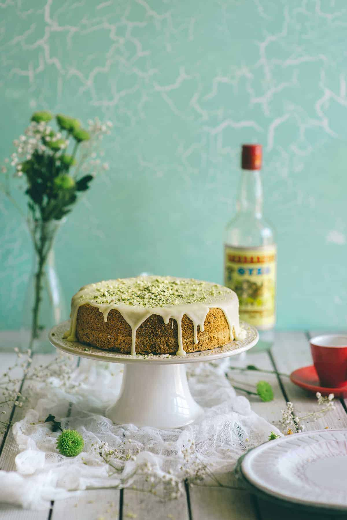 a cake flavoured with ouzo and pistachios. It is covered in a thick orange flavoured icing