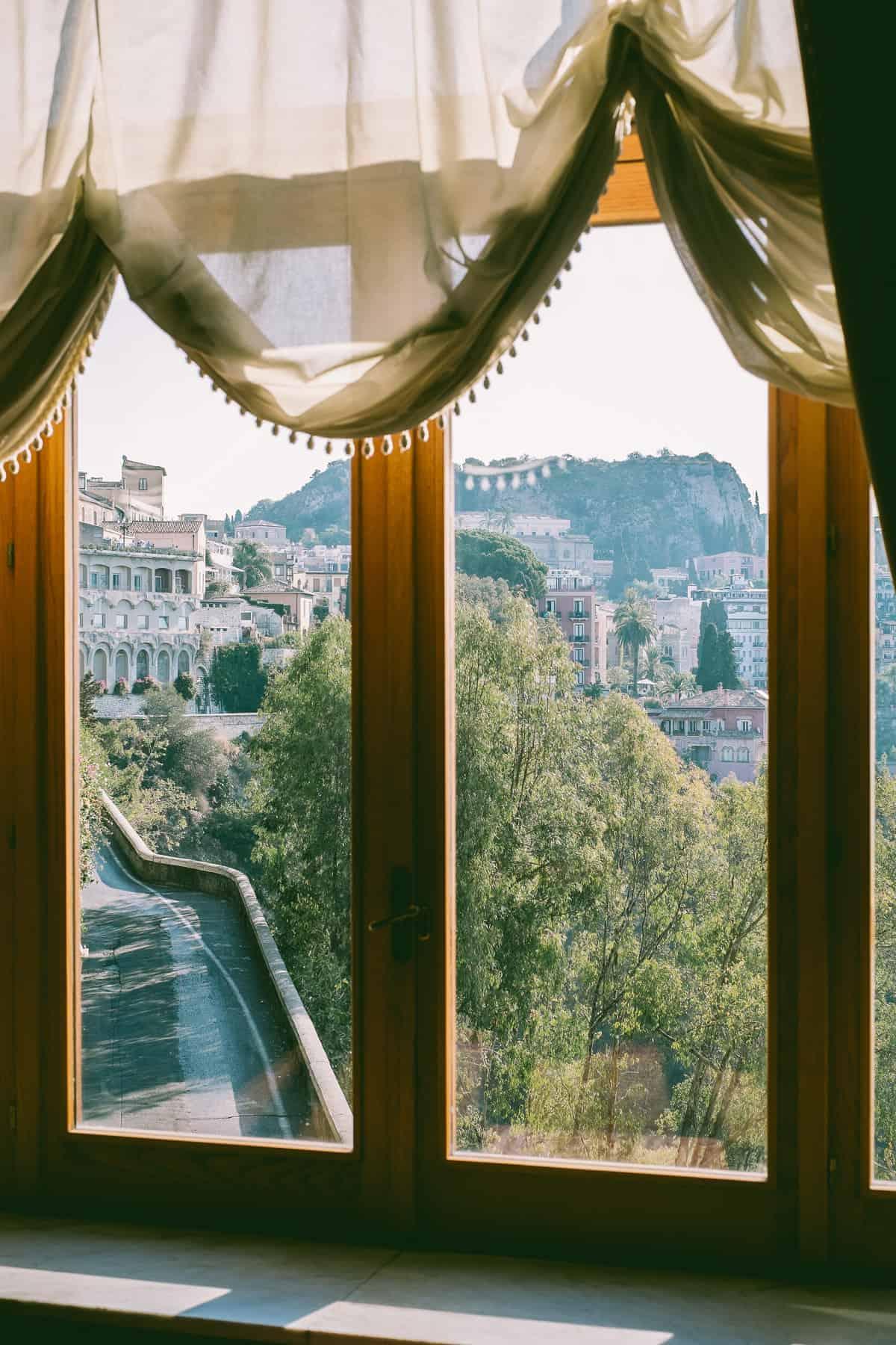 looking onto Taormina from the ornate windows of the San Domenico Palace Hotel Taormina Sicily