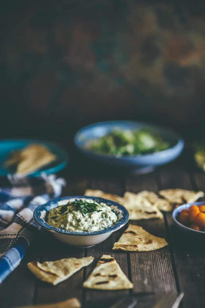 a bowl of tzatziki made with the addition of avocado. Served with Greek pita bread on the side