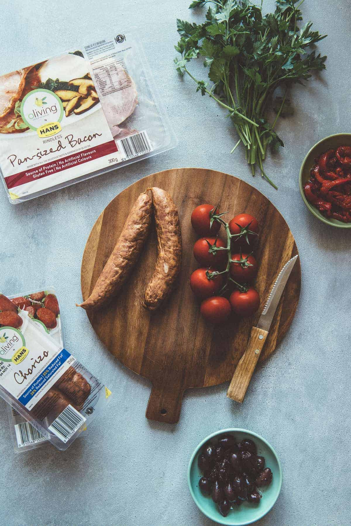 sausages and tomatoes on a chopping board with herbs