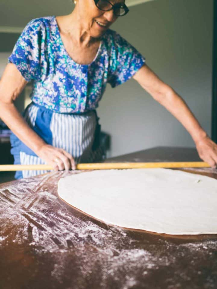 Greek mother rolling out homemade fillo dough for a Greek spinach pie