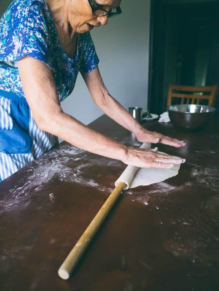 Greek mother rolling out homemade fillo dough on a table for spanakopita