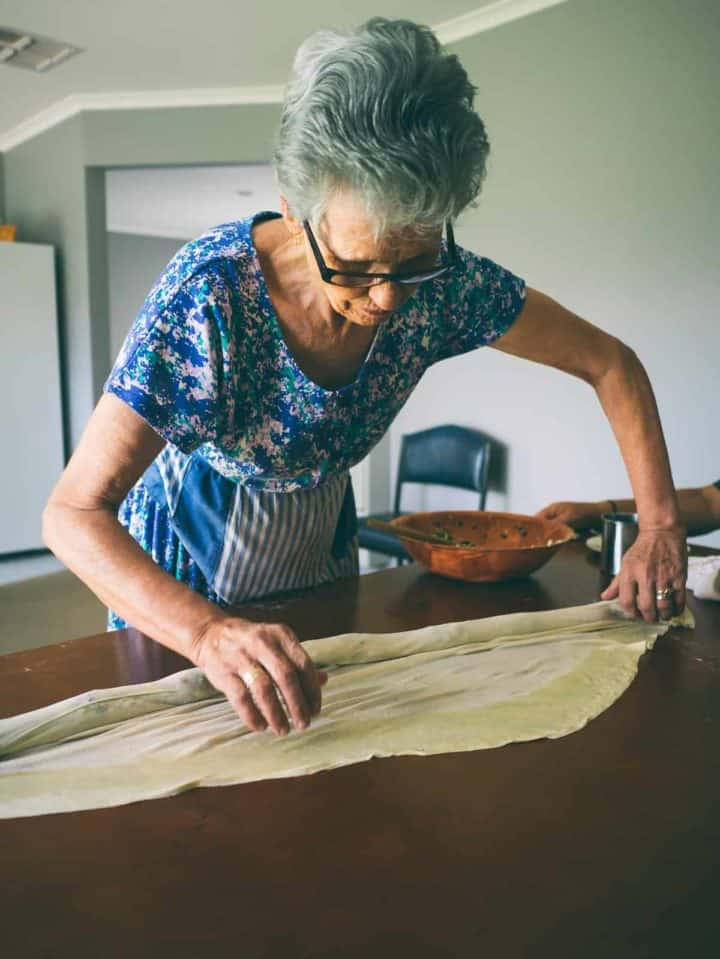 Greek mother shaping traditional homemade spanakopita on a table