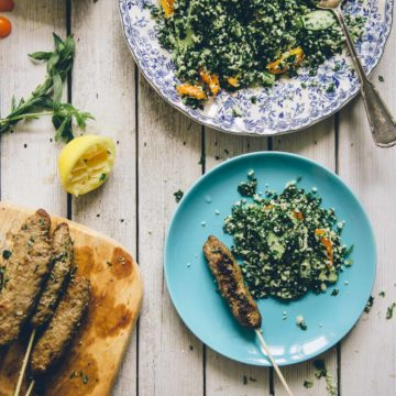 Middle Eastern beef koftas served with a grain free tabouli on a table