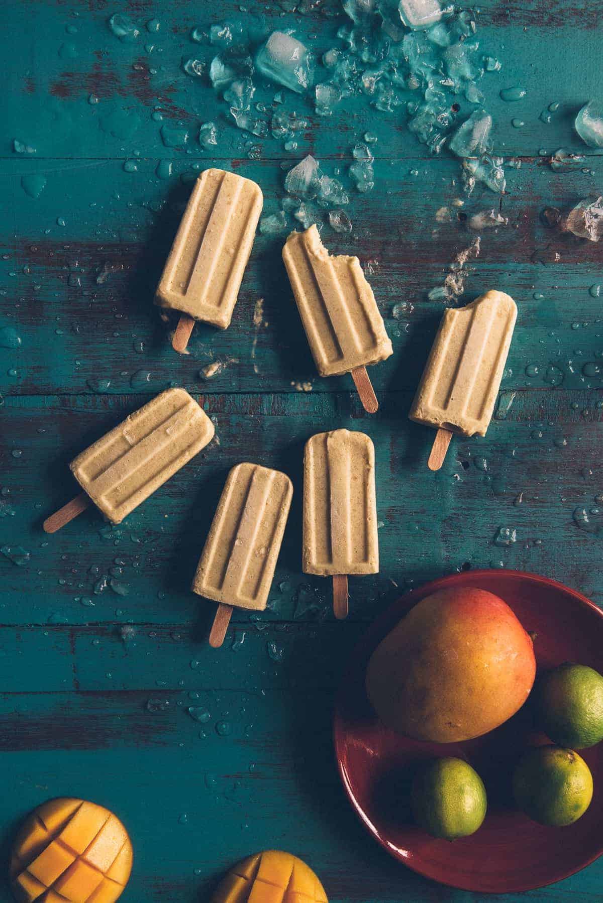 mango coconut and lime popsicles on a table with mangoes and limes