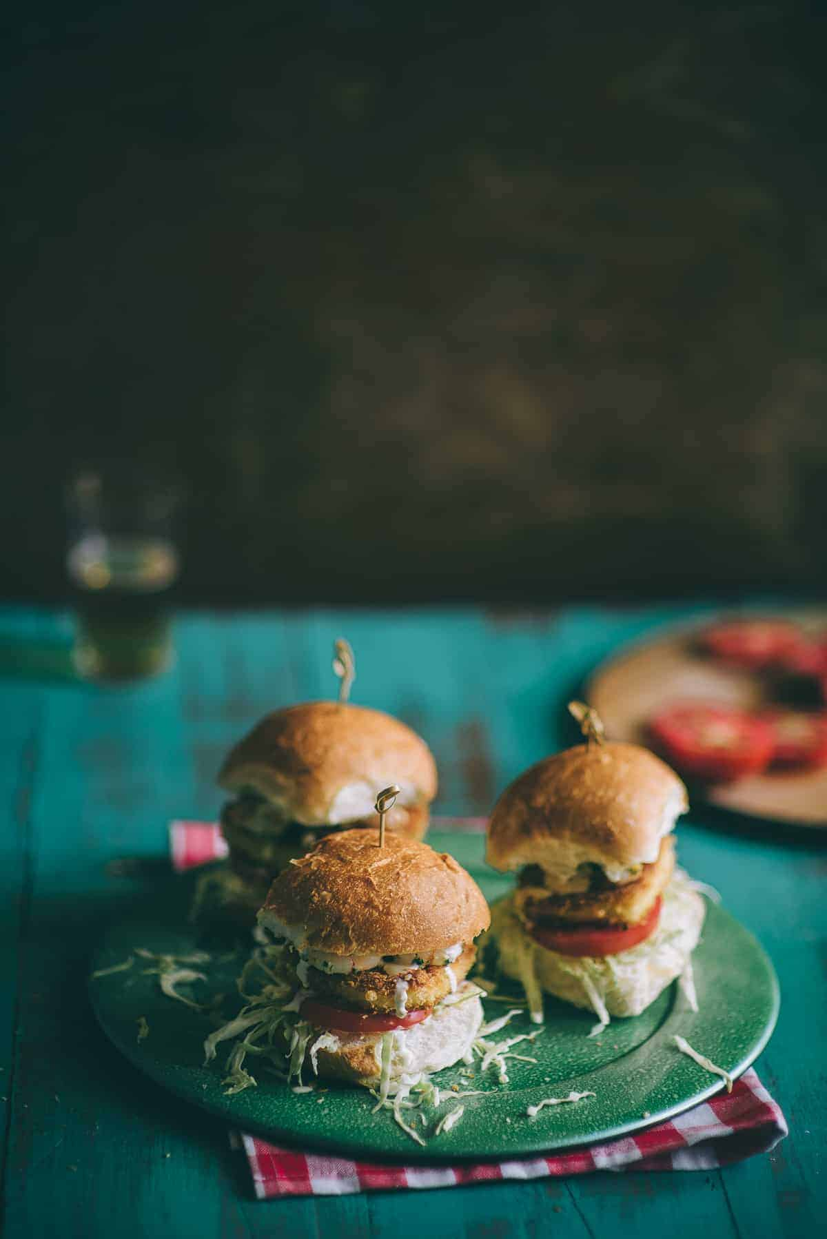 three burgers on a green plate on a rustic green table