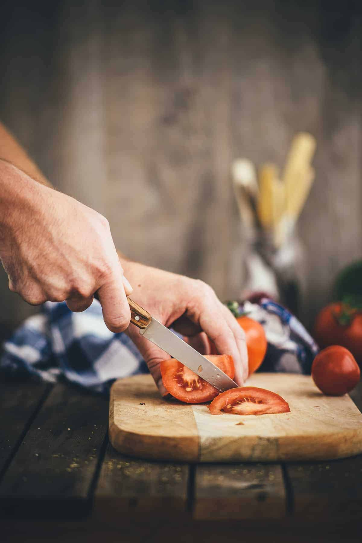 tomatoes being sliced on chopping board