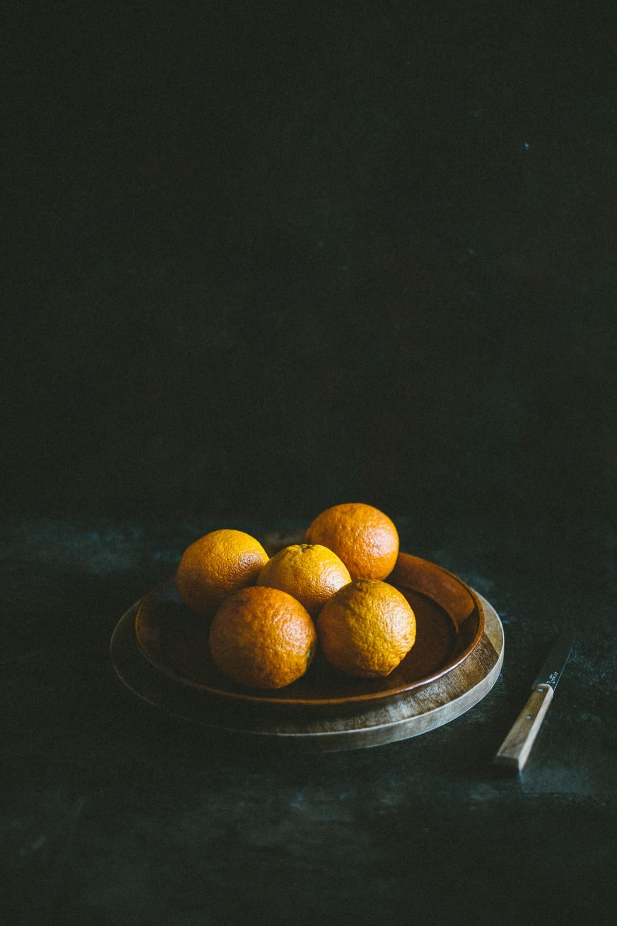 five blood oranges on a plate