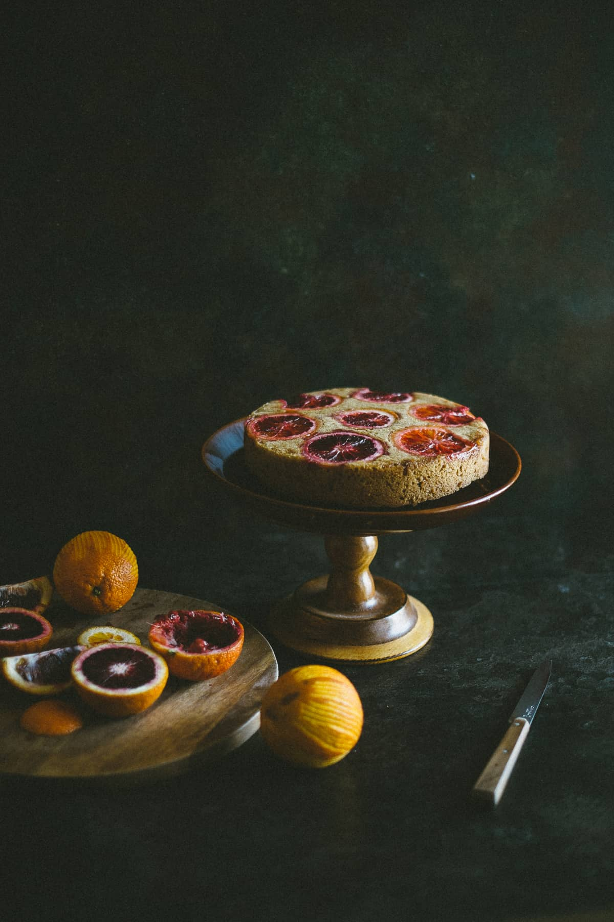 A cake made with blood oranges on a cake stand