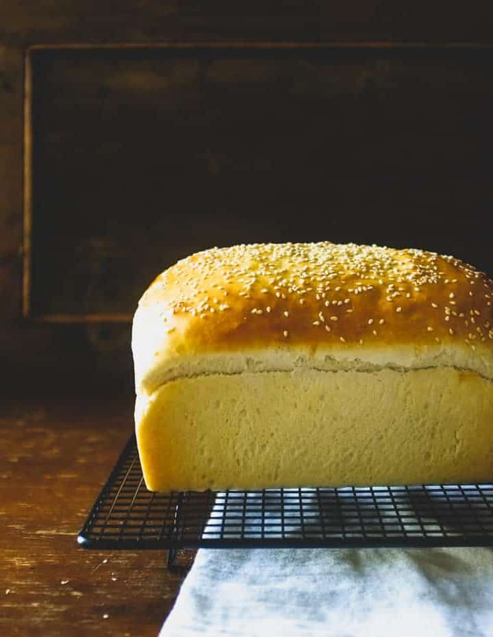 a full sized loaf of brioche bread cooling on a rack