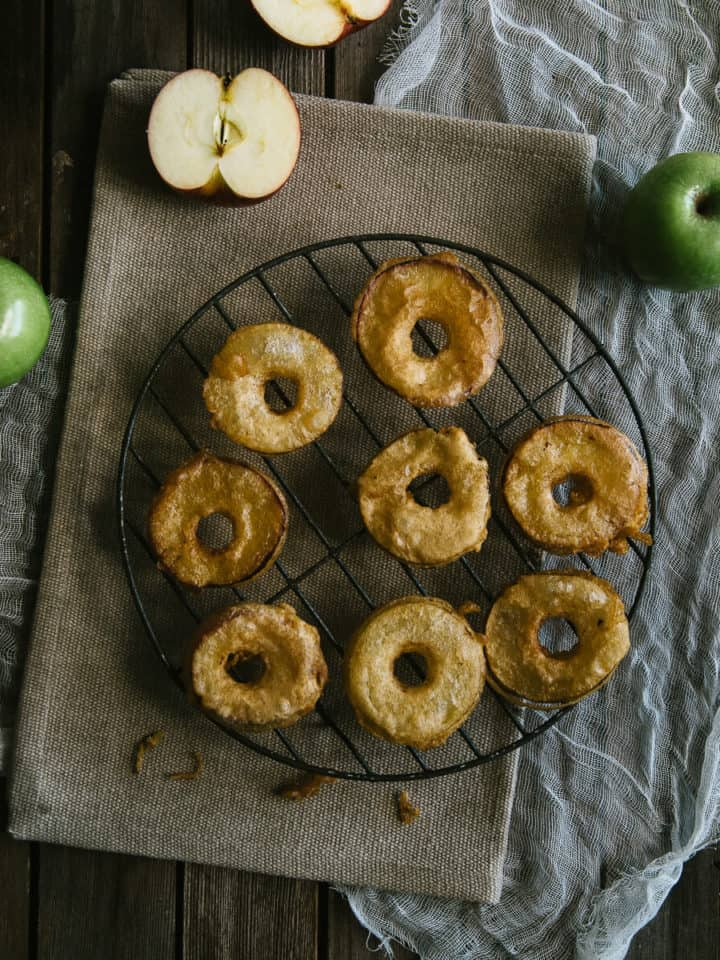 cooked apple fritters on a wire rack