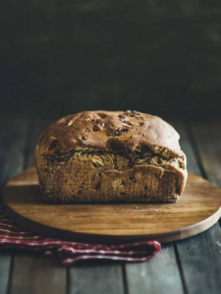 a loaf of fig and walnut bread on a chopping board