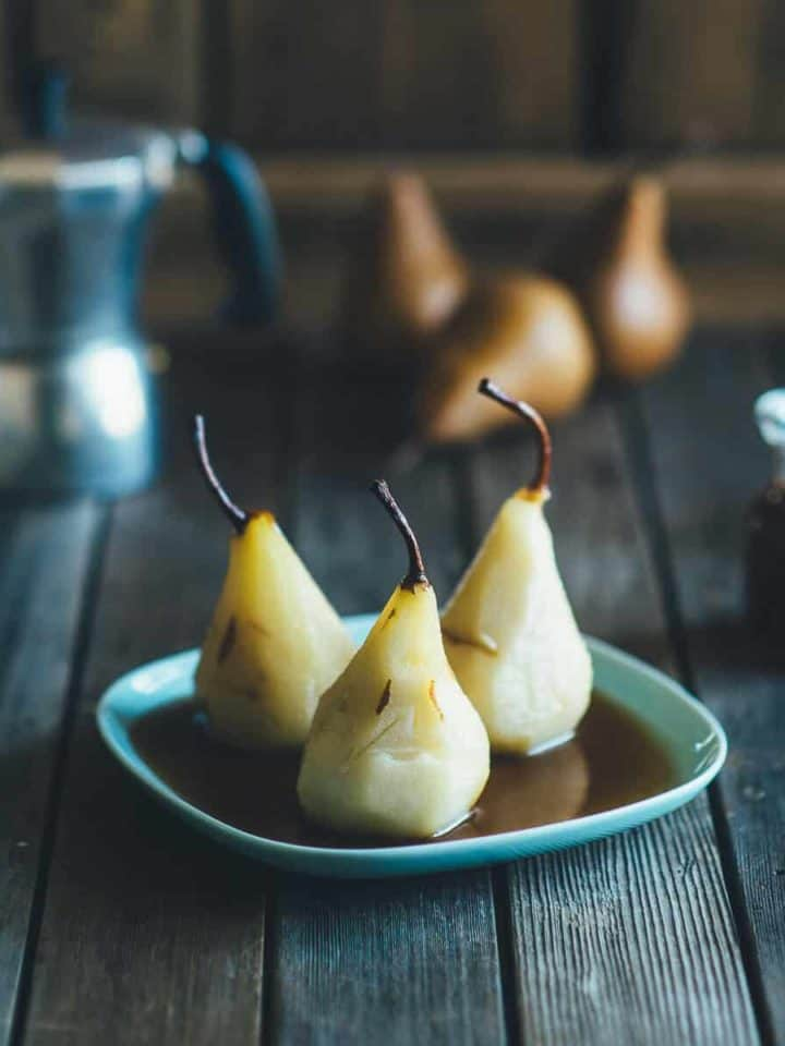 poached pears served on a blue plate