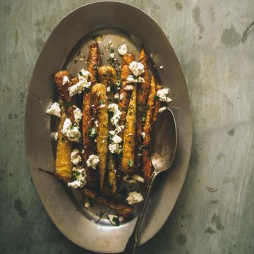 roasted carrots topped with goats cheese served on a platter