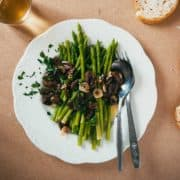 cooked asparagus served with an olive salsa served on a white plate