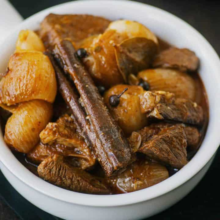 braised beef with onions and cinnamon served in a white bowl
