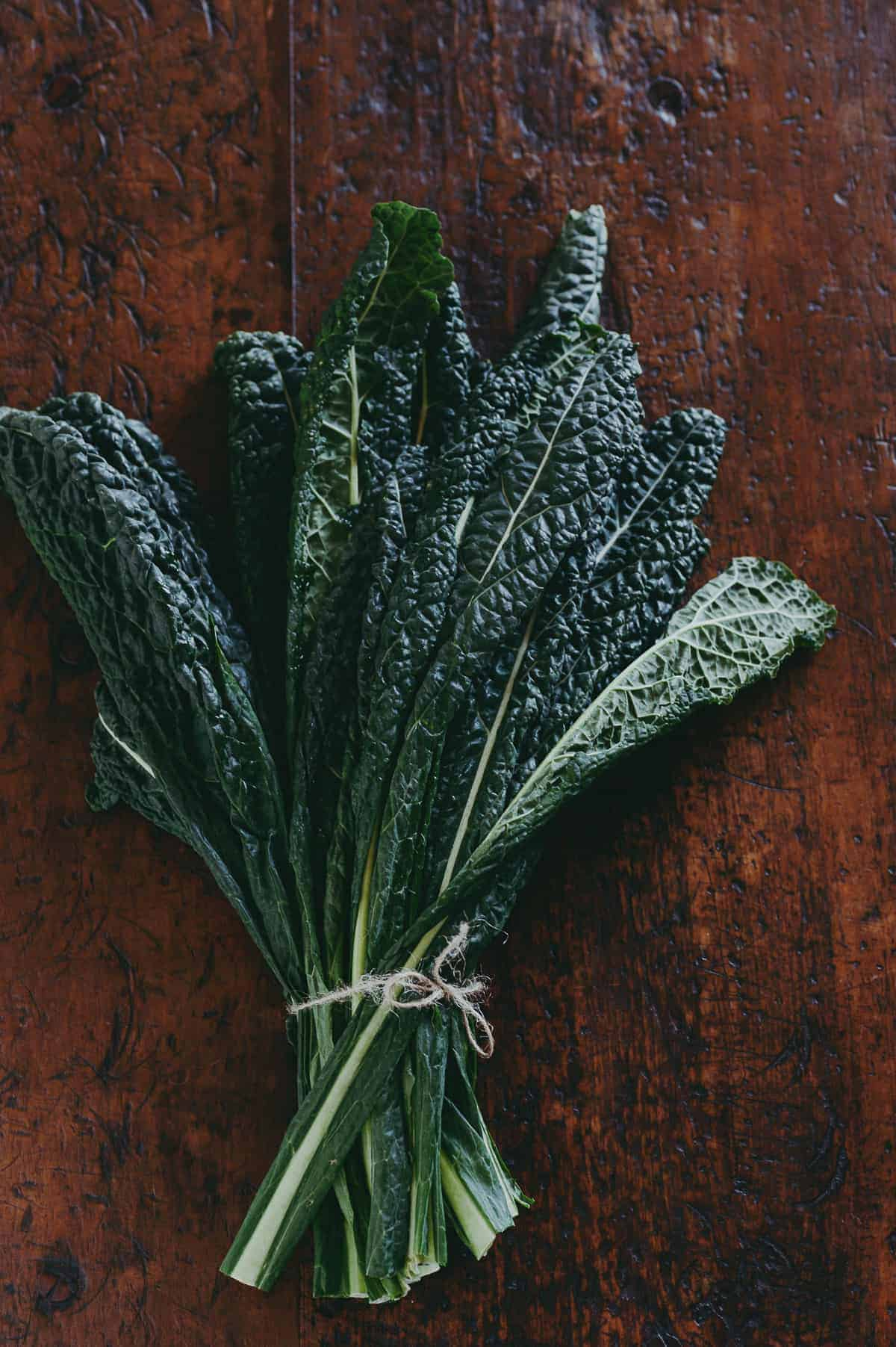 a bunch of cavolo nero (black kale) on a wooden table