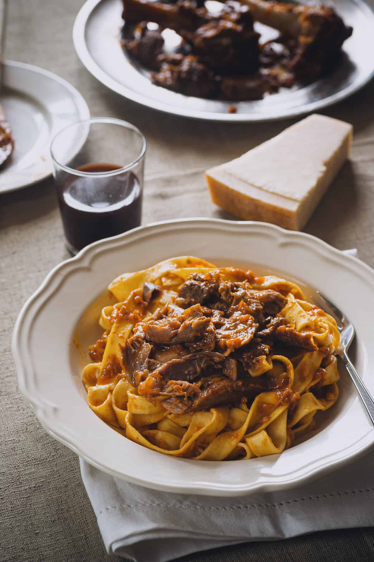 a plate of pasta topped with a meat sauce made from lamb shanks