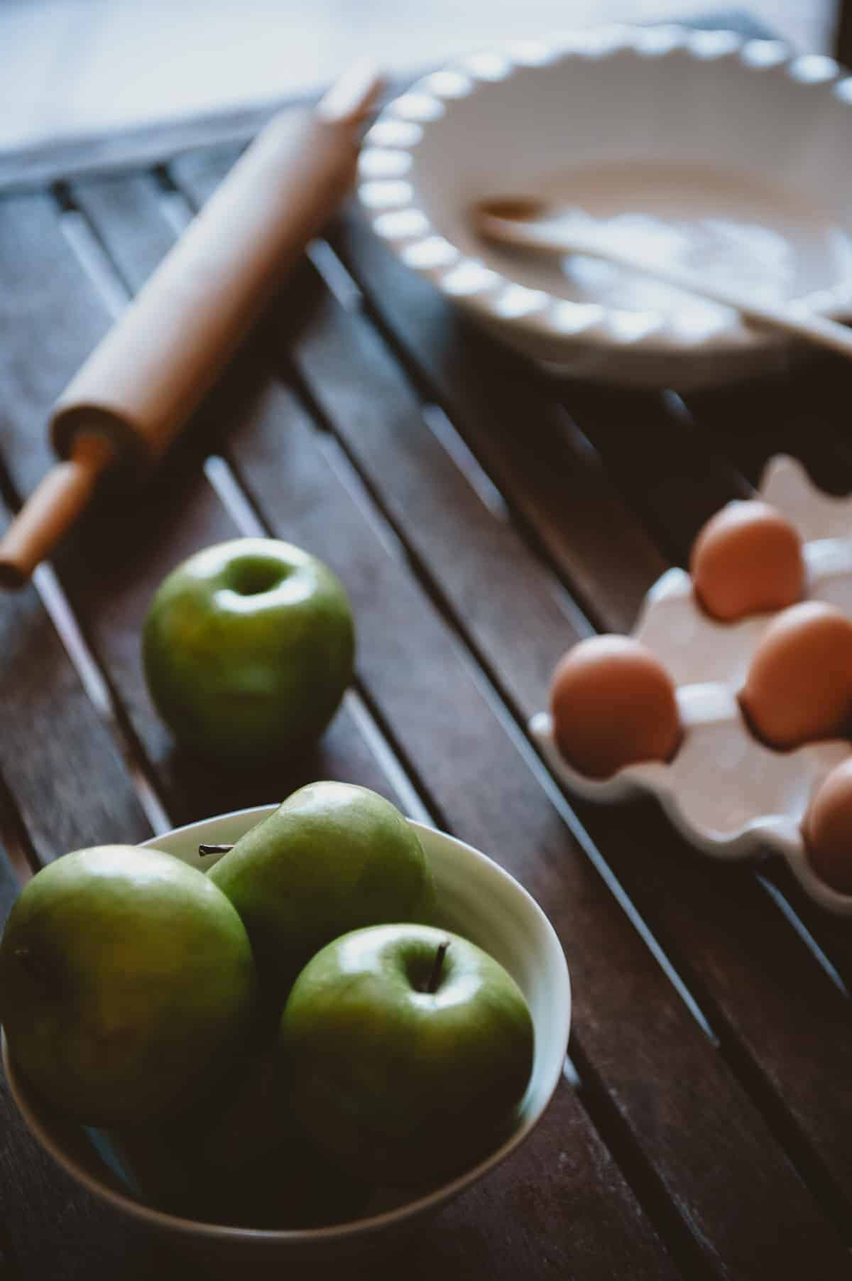 apples, eggs, a rolling pin and a dish too make apple pie on a wooden table