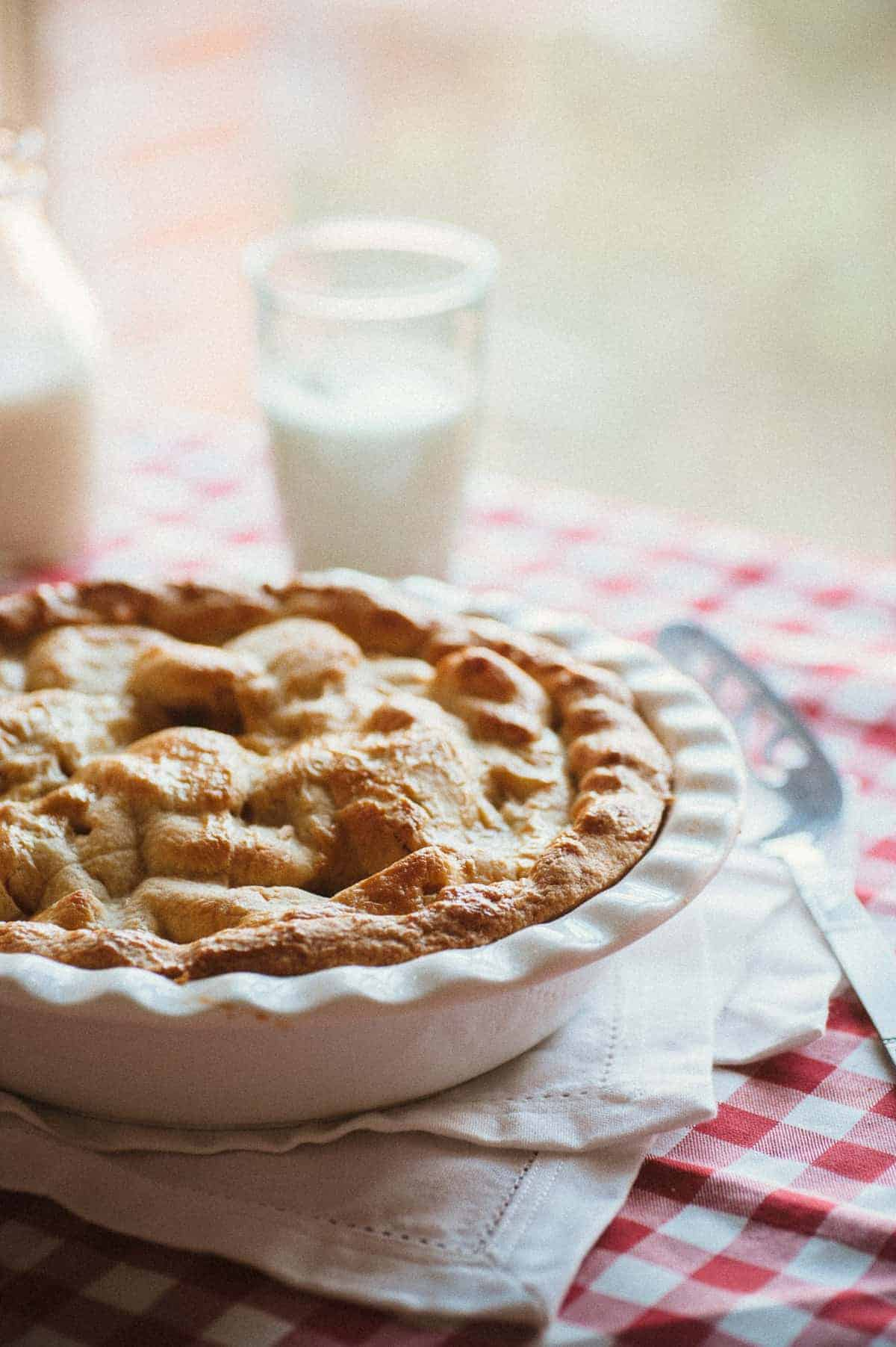 a deep dish apple pie served a red and white tablecloth