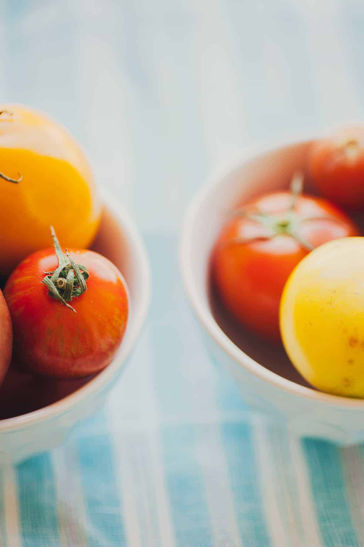 2 bowls filled with yellow and red tomatoes