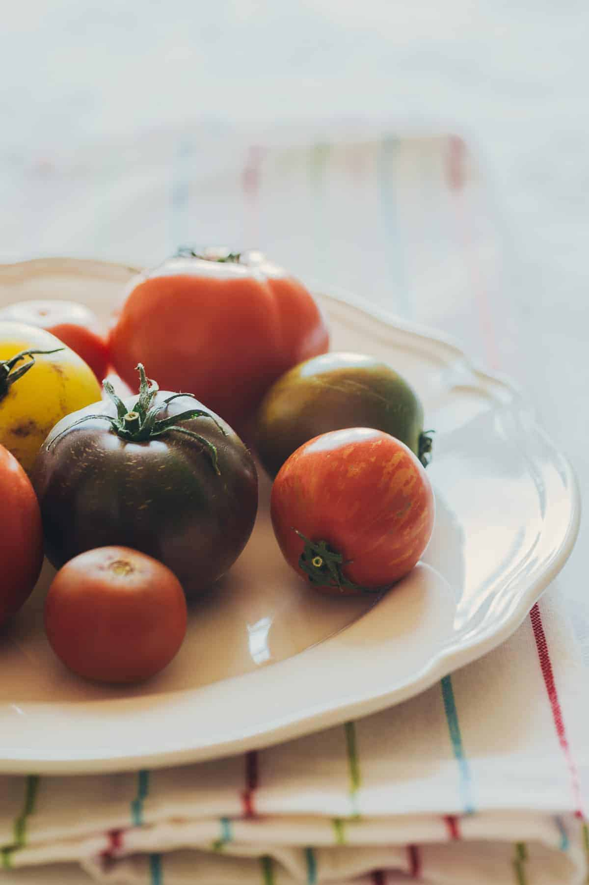 a white plate filled with a variety of coloured tomatoes