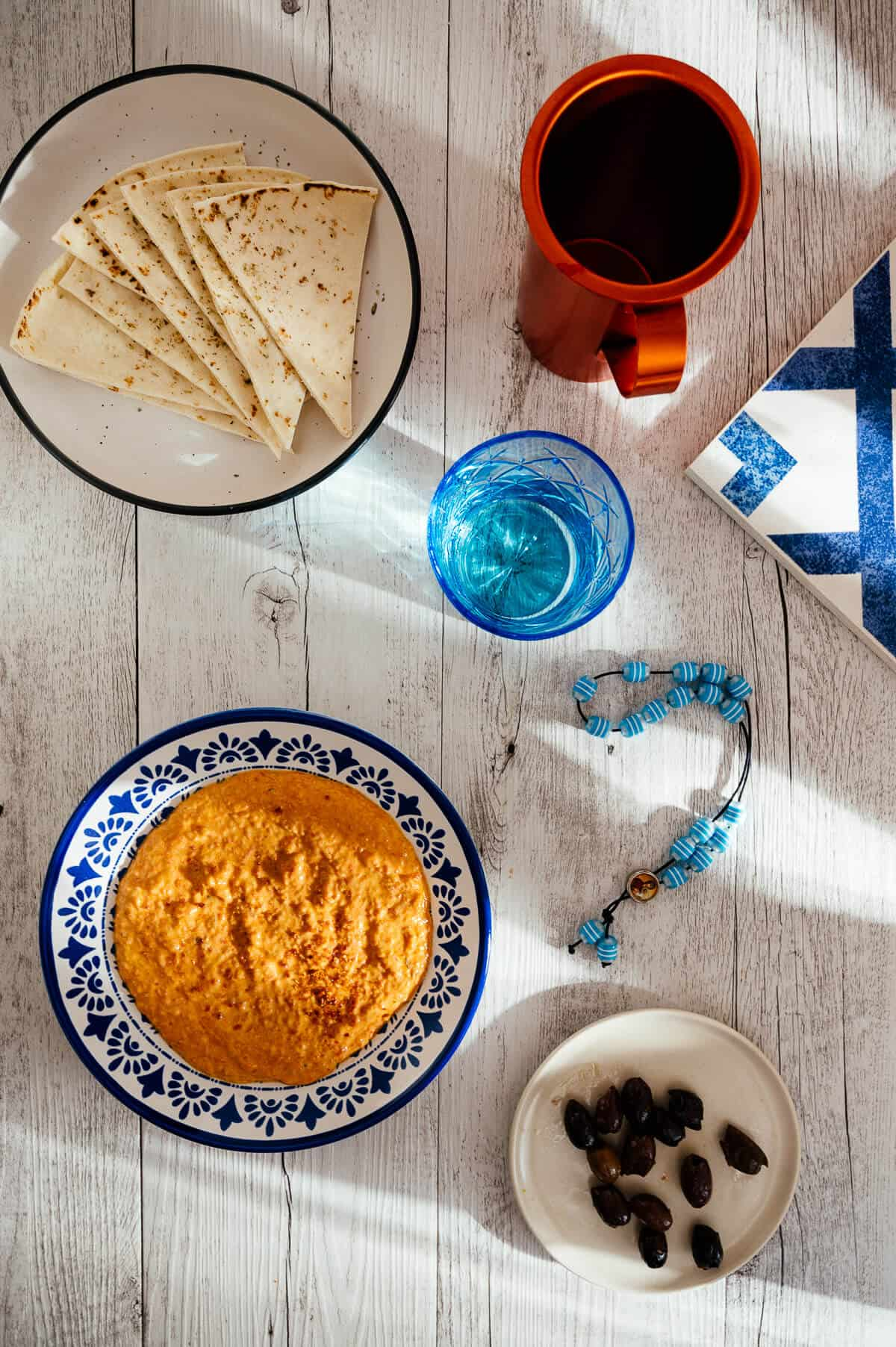 a top down view of a white table filled with greek dip, pita bread, wine, olives and a glass
