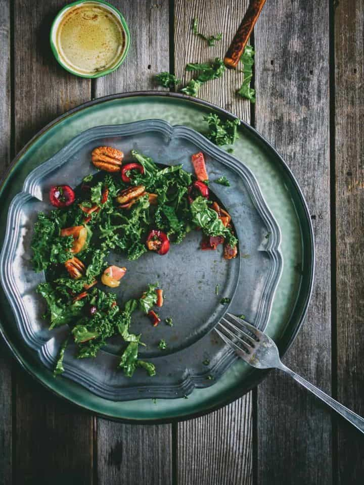 a birds eye view of a kale salad served on a silver plate on a wooden table