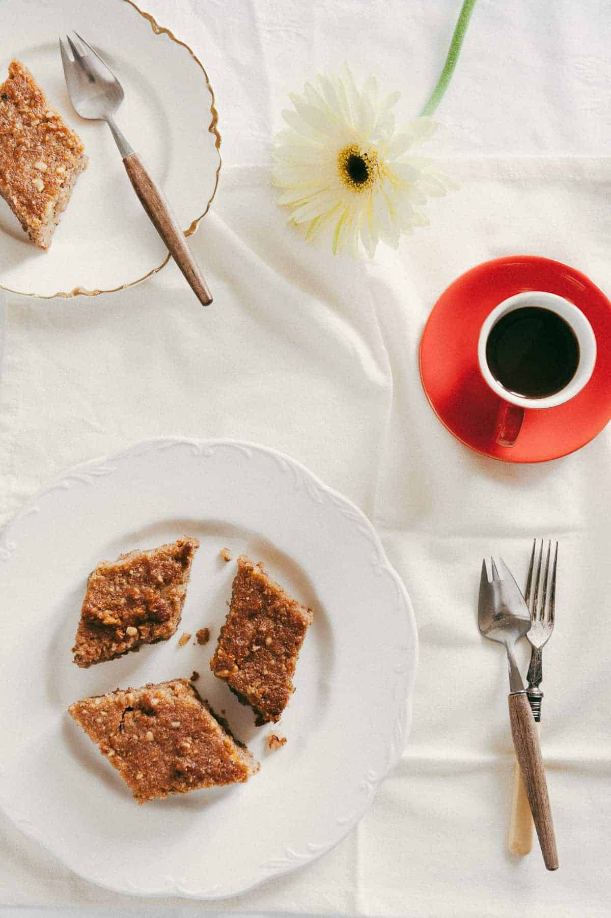 top down view of three slices of Greek walnut cake served on a white plate with a coffee and flowers