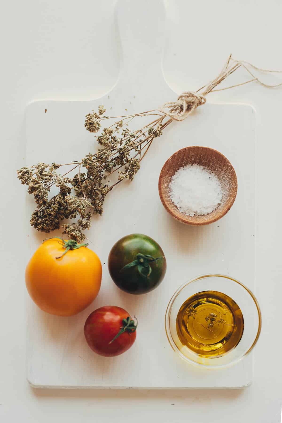 tomatoes, salt, olive oil and oregano on a white chopping board