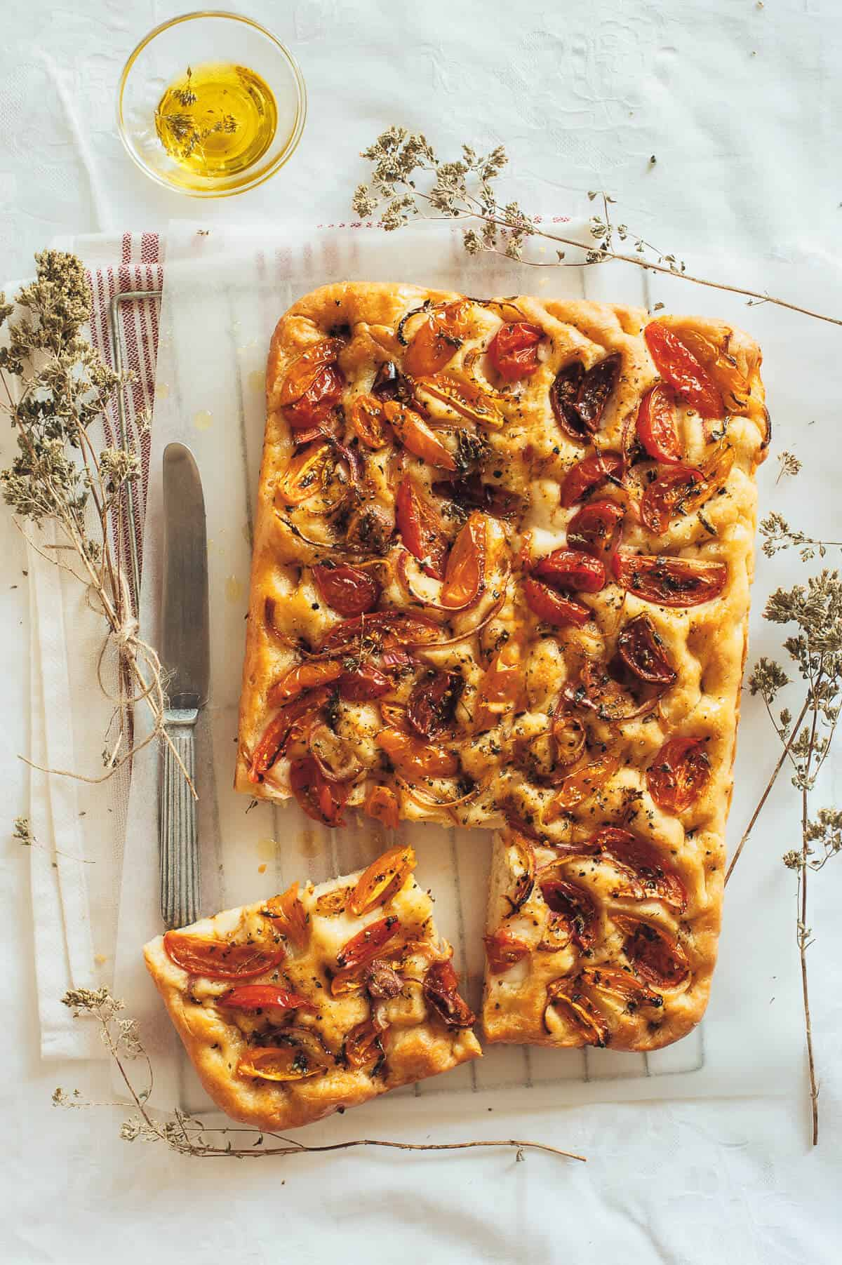 a top down view of a Greek flatbread called ladenia topped with tomatoes, oregano and red onions