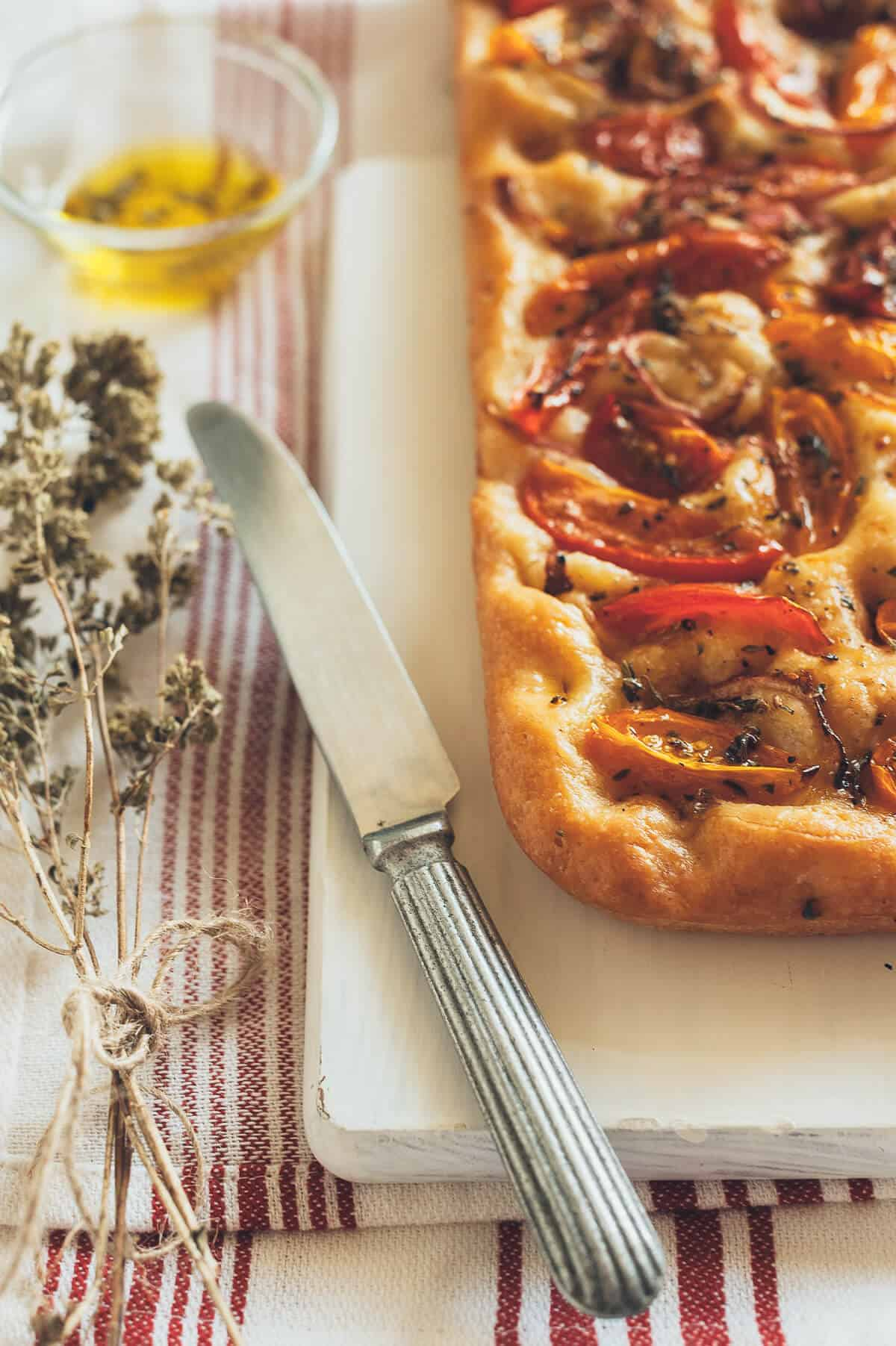 ladenia - a Greek flatbread topped with tomatoes, onions, olive oil and oregano presented on a white board with a knife next to it.