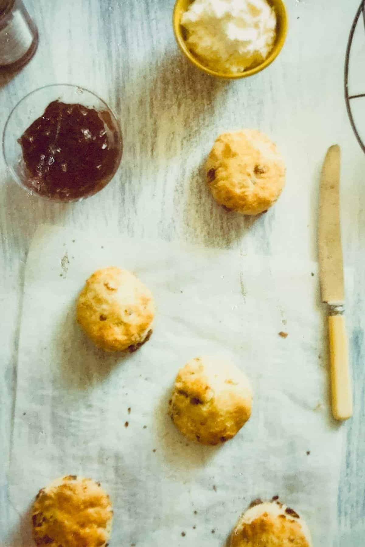 lemon and date scones on a table with jam and a knife