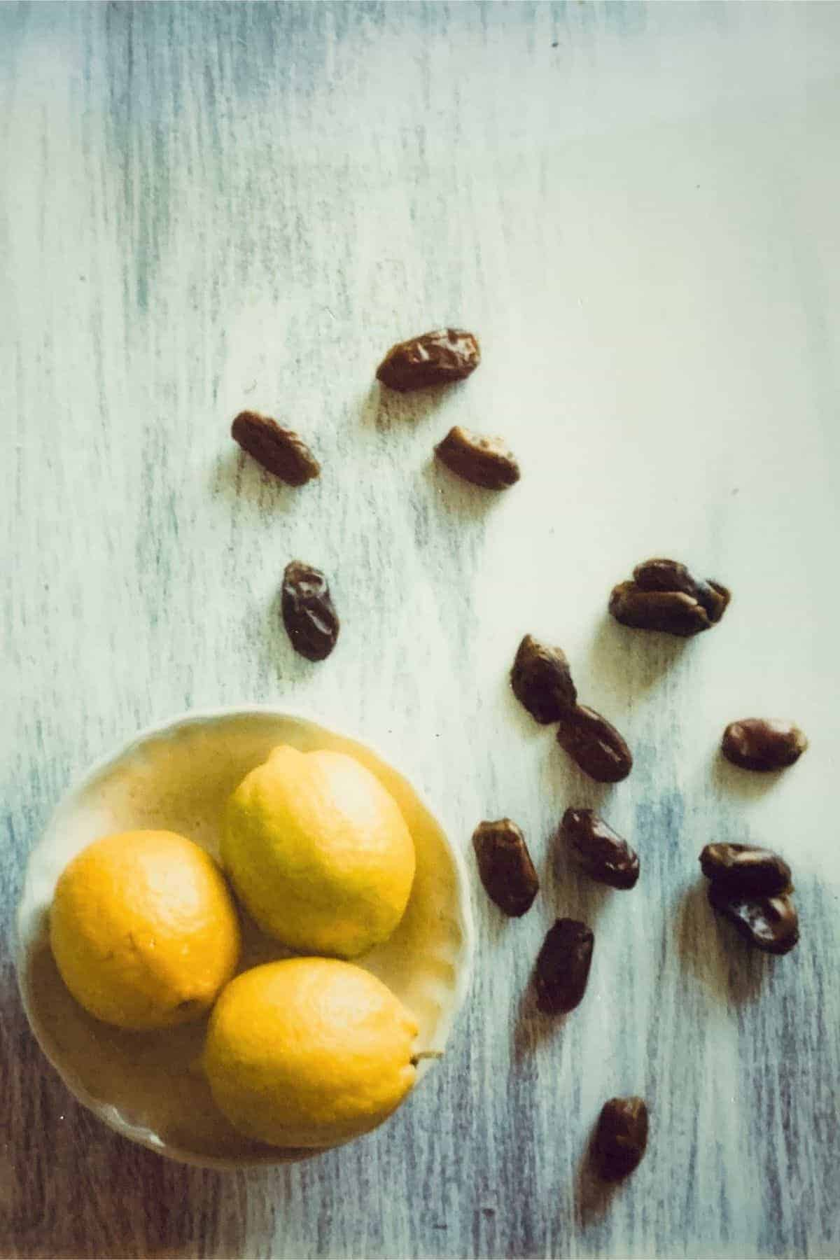 a bowl of lemons and scattered dates on a table