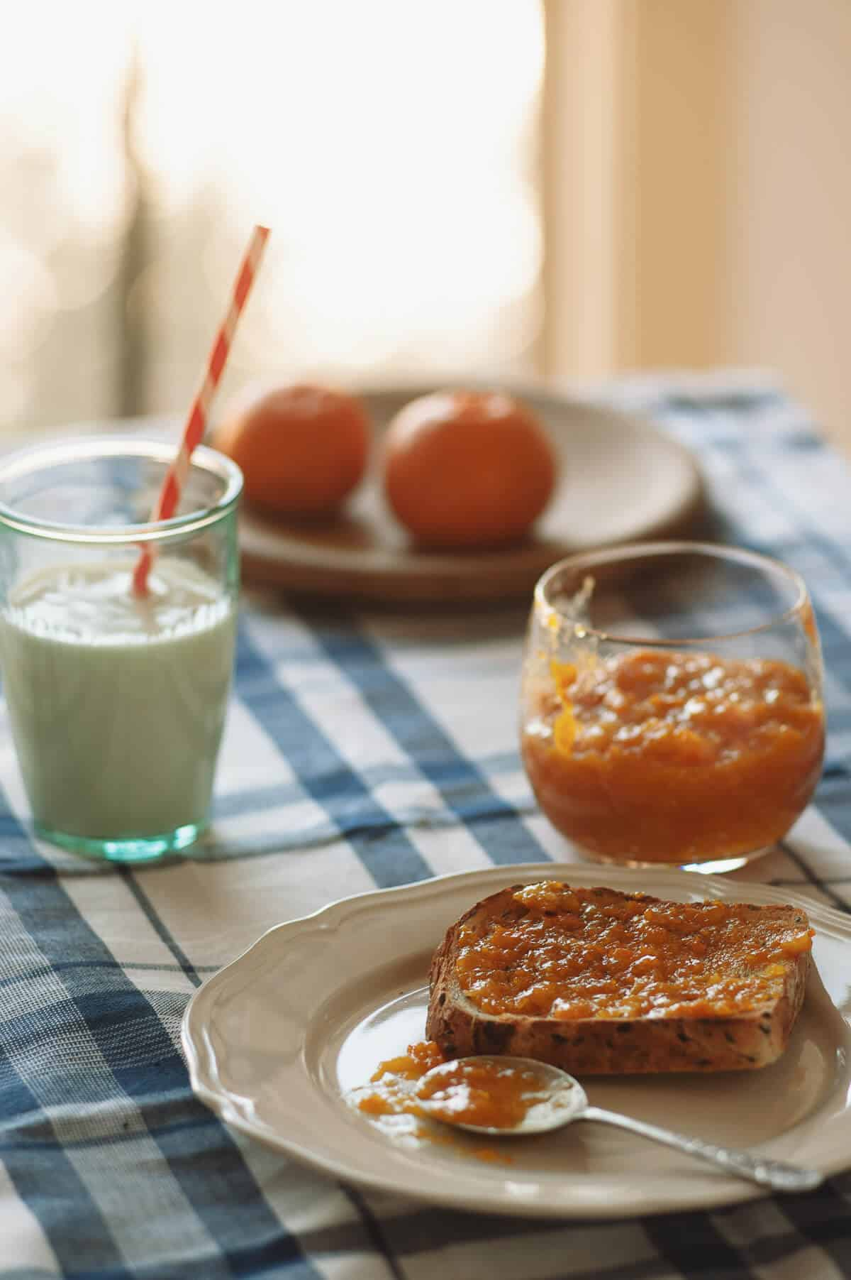 a slice of toast with mandarin jam served on a plate with a glass of milk