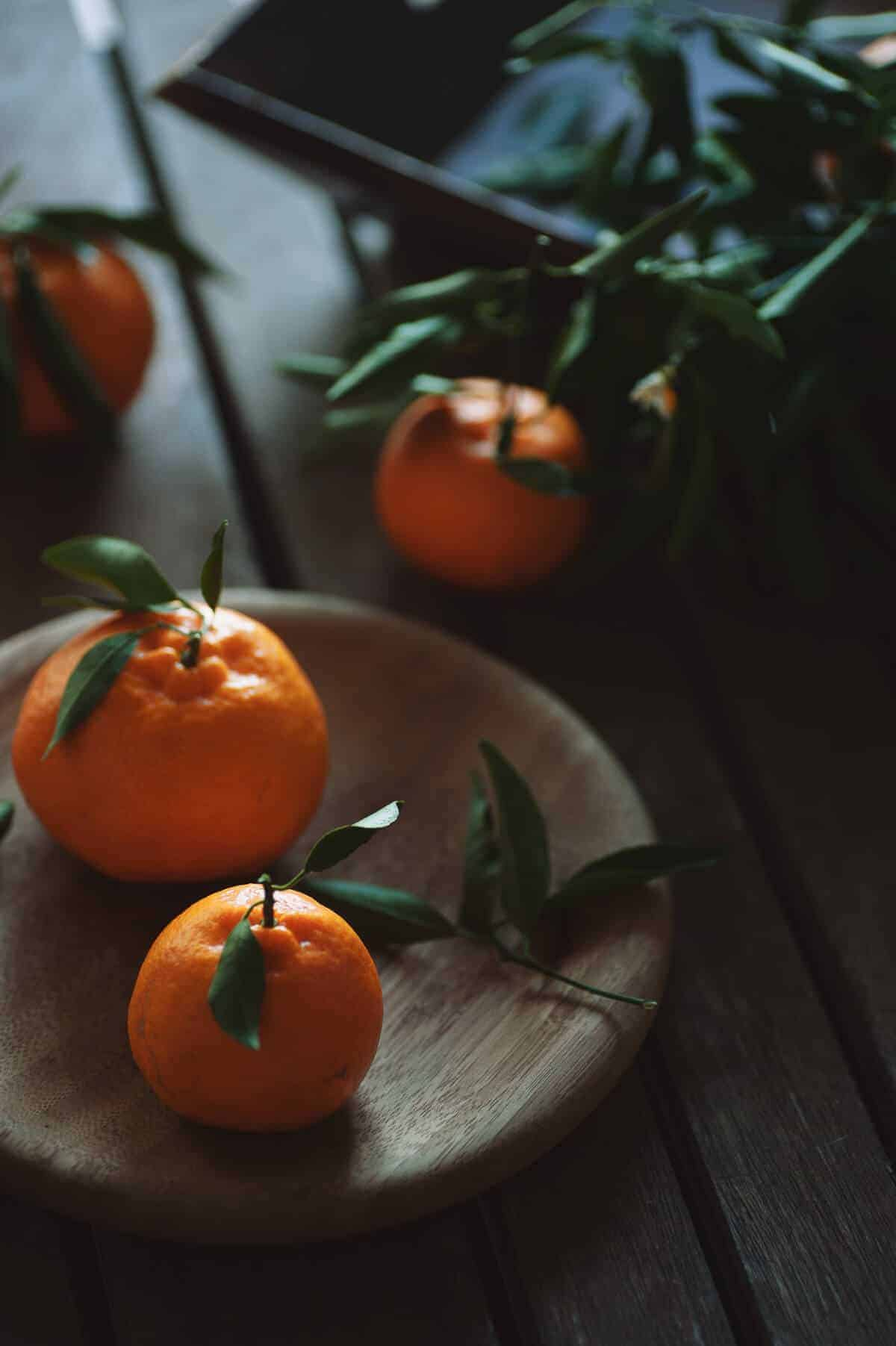 four mandarins on a wooden table