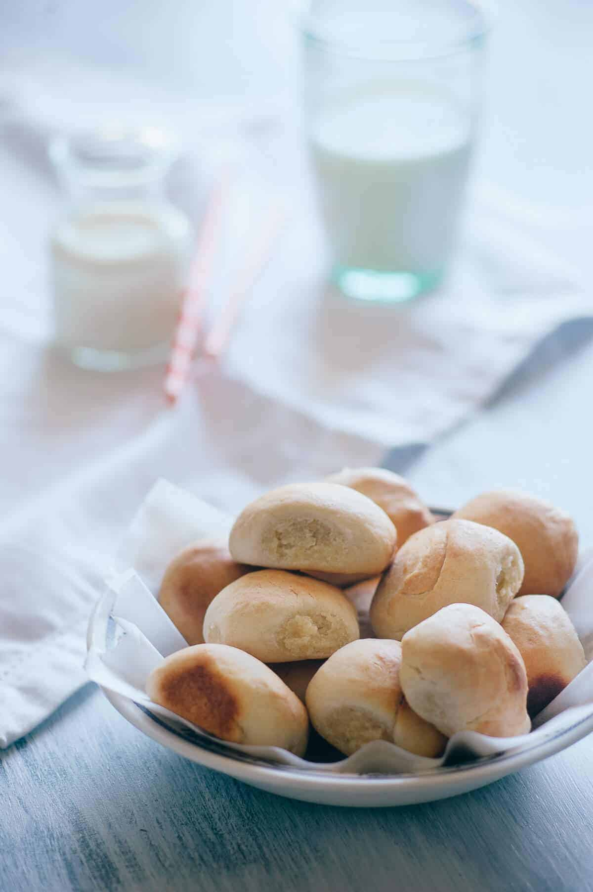 a bowl of homemade sweet bread rolls on a light blue table