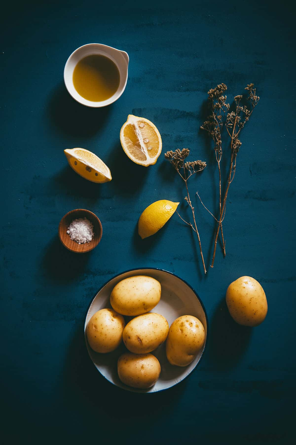 potatoes, olive oil, oregano and lemons laid out on  a blue table