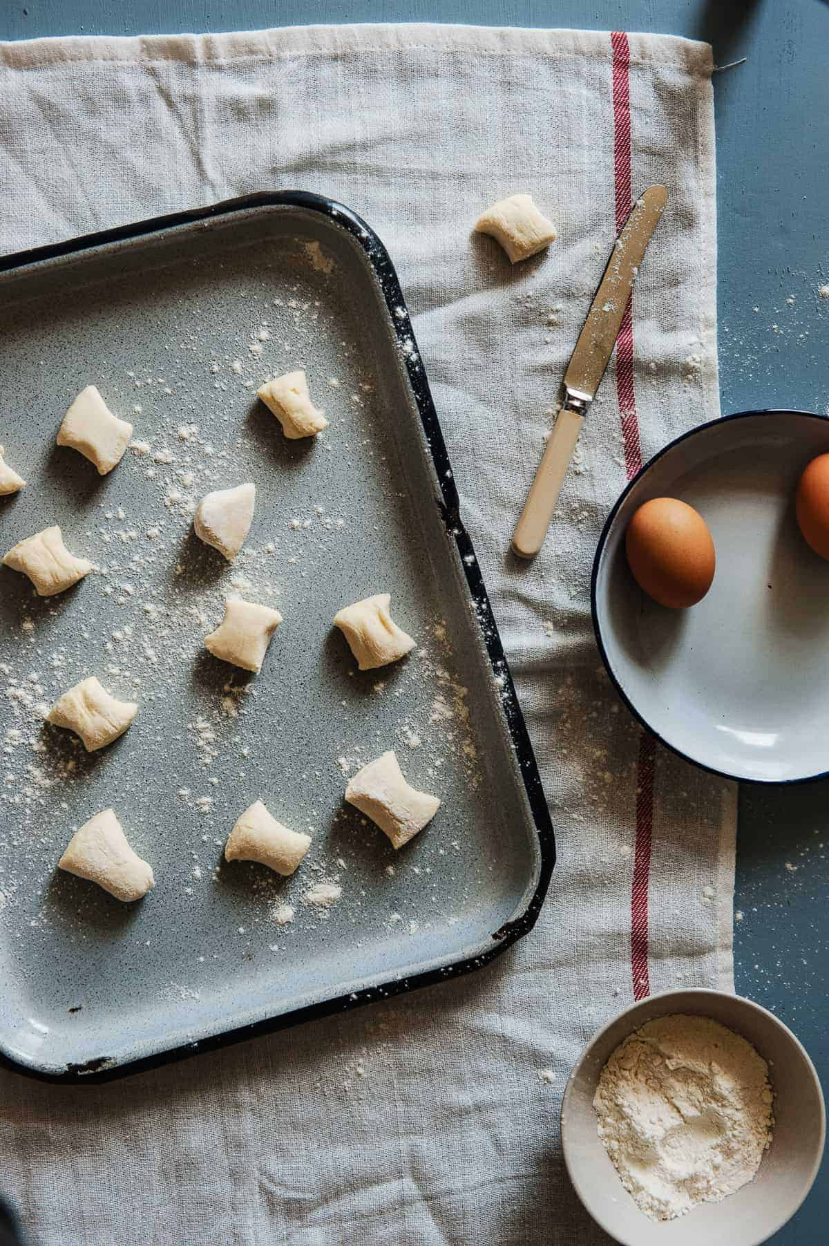 top down view of ricotta gnocchi on a tray with eggs and flour next to them