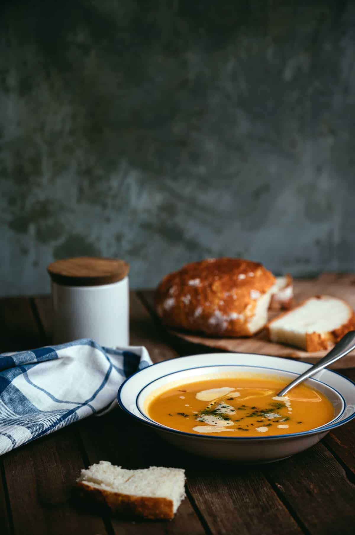 a bowl of soup on a table with fresh bread