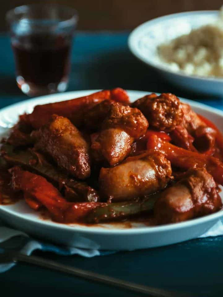 a plate filled with sausages and peppers cooked in a tomato sauce