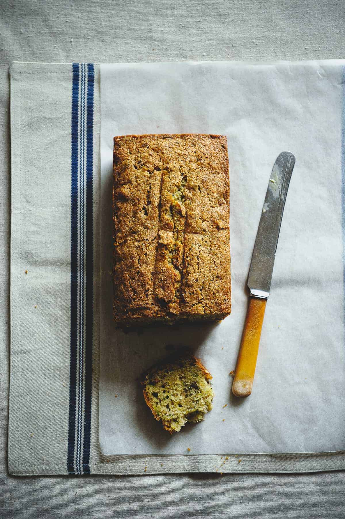 top down view of a zucchini bread on a table with a knife next to it