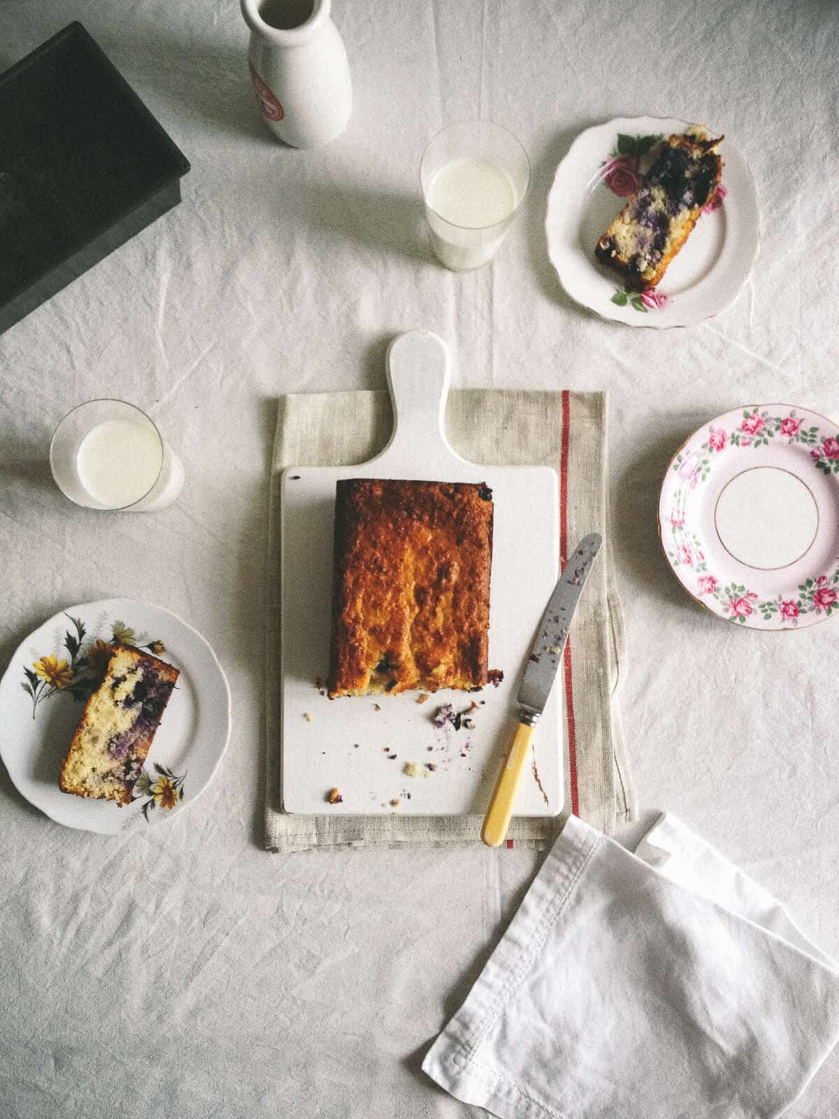 a to[pp down view of a cake on table with plates and slices of cake