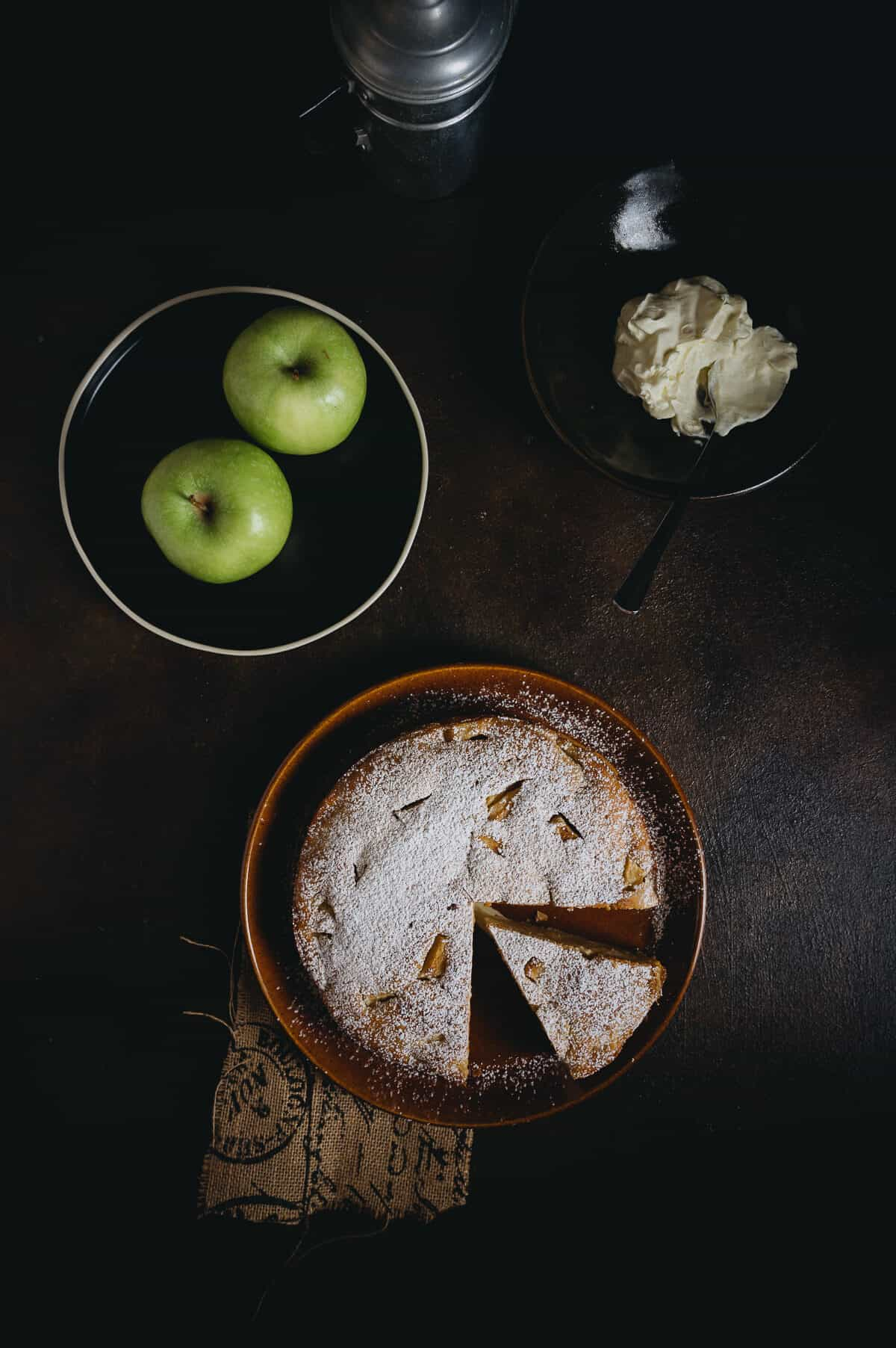 a sliced apple cake on a table with whipped cream and two apples on a dark plate