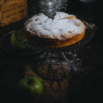 a cake on a cake stand being dusted with powdered sugar