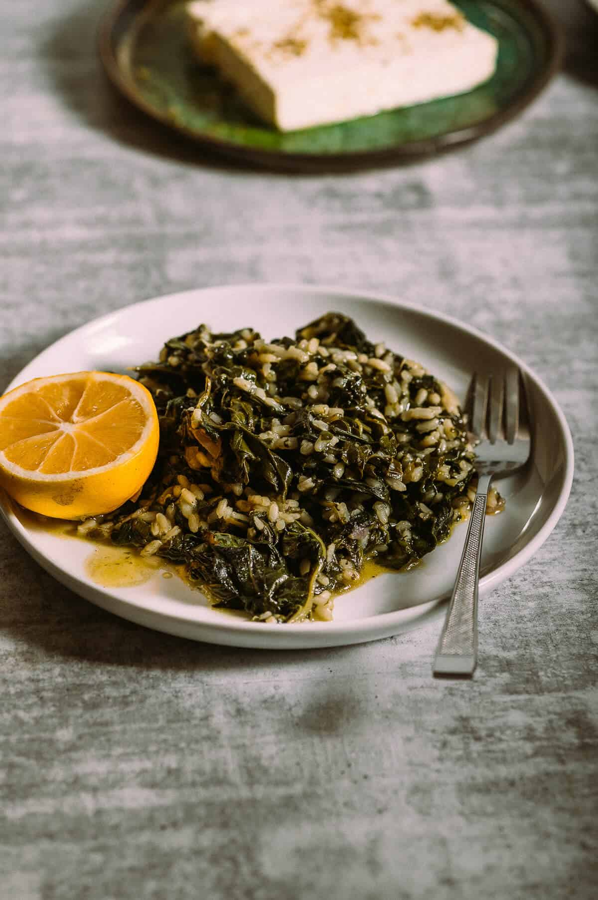 a white plate filled with cooked spinach and rice served with a lemon wedge and feta cheese