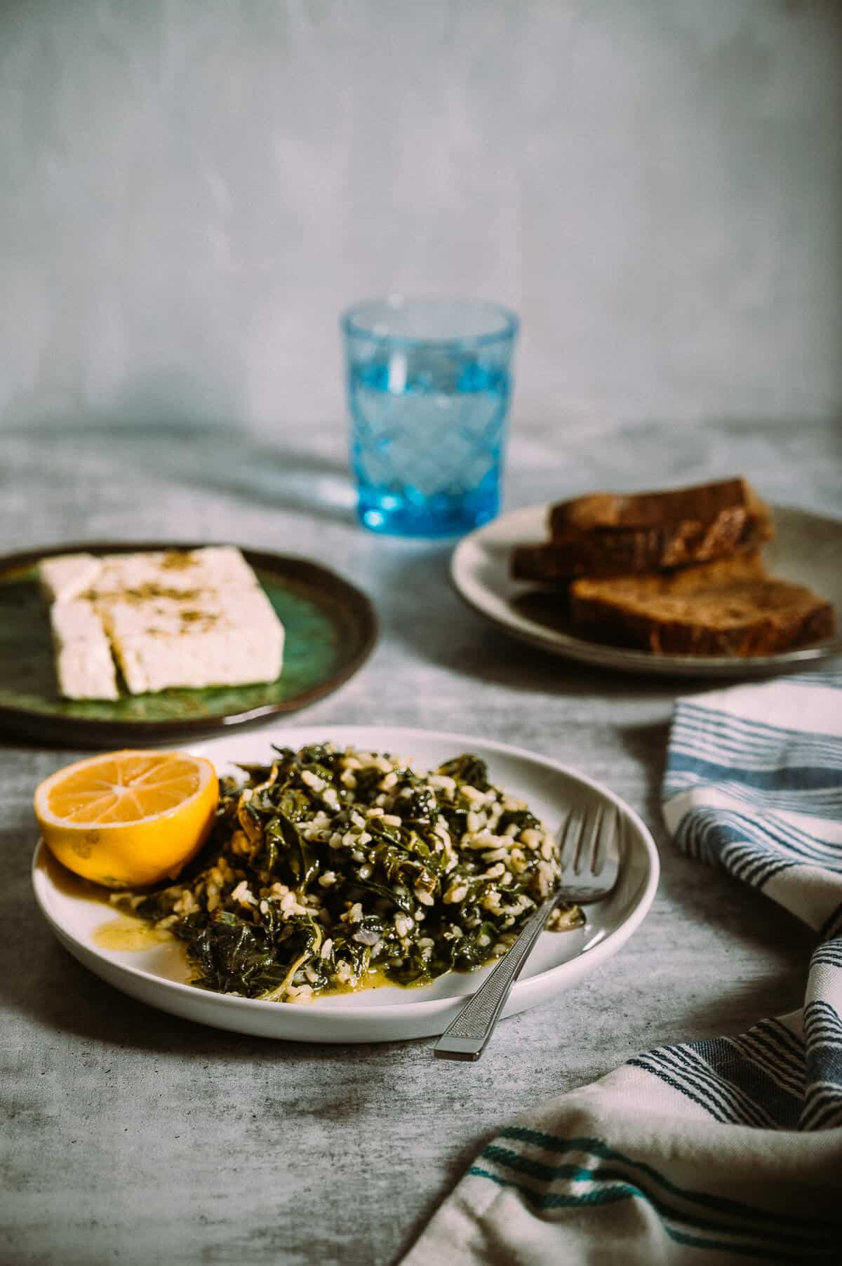 a plate filled with cooked spinach and rice served with feta cheese and bread on a grey table