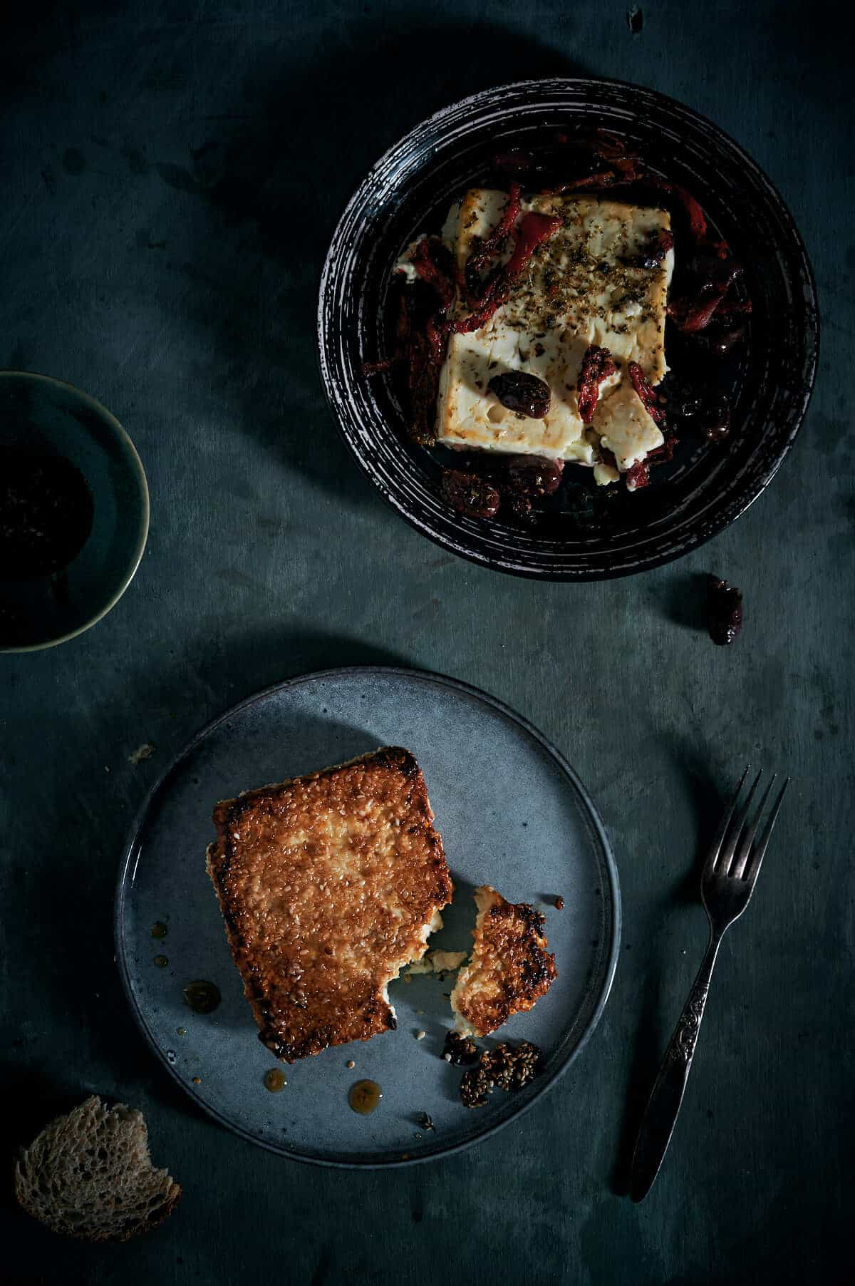two plates on a table with a serve of baked feta cheese